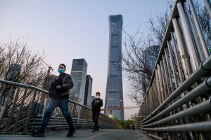 BEIJING, CHINA - APRIL 07: Chinese commuters wear protective masks as they cross a footbridge during rush hour in the central business district on April 7, 2020 in Beijing, China. China recorded for the first time since January 21st no coronavirus-related deaths. With the pandemic hitting hard across the world, officially the number of coronavirus cases in China is dwindling, ever since the government imposed sweeping measures to keep the disease from spreading. For more than two months, millions of people across China have been restricted in how they move from their homes, while other cities have been locked down in ways that appeared severe at the time but are now being replicated in other countries trying to contain the virus. Officials believe the worst appears to be over in China, though there are concerns of another wave of infections as the government attempts to reboot the worlds second largest economy. In Beijing, it is mandatory to wear masks outdoors, some retail stores still operate on reduced hours, restaurants employ social distancing among patrons, and tourist attractions at risk of drawing large crowds remain closed or allow only limited access. Monitoring and enforcement of virus-related measures and the quarantine of anyone arriving to Beijing is carried out by neighborhood committees and a network of Communist Party volunteers who wear red arm bands. Since January, China has recorded more than 81,000 cases of COVID-19 and at least 3200 deaths, mostly in and around the city of Wuhan, in central Hubei province, where the outbreak first started. (Photo by Kevin Frayer/Getty Images)
